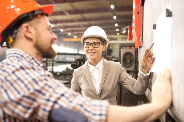 Gelukkig jonge vrouwelijke ingenieur in helm wijzend op papier op whiteboard tijdens het maken van de presentatie voor collega