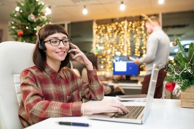 Gelukkig jonge vrouwelijke operator met headset raadplegen van klanten online voor laptop in kantoor op eerste kerstdag