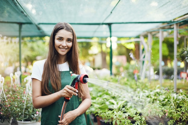 Gelukkig jonge vrouwelijke tuinman planten water geven in de eigenaar geëxploiteerde kas winkel.