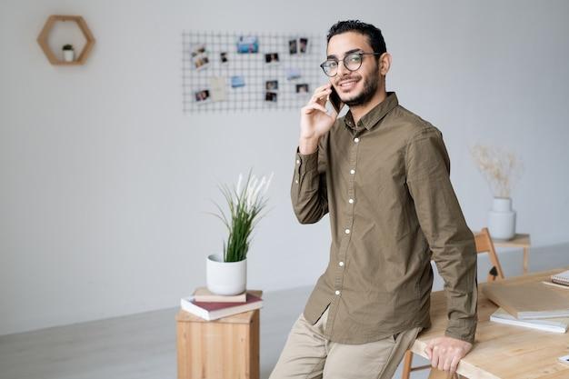Gelukkig jonge zakenagent permanent door tafel in kantoor tijdens het raadplegen van een van de klanten door smartphone