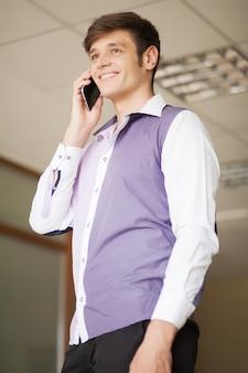 Gelukkig jonge zakenman bellen op smartphone via kantoorruimte
