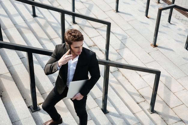 Gelukkig jonge zakenman buiten lopen