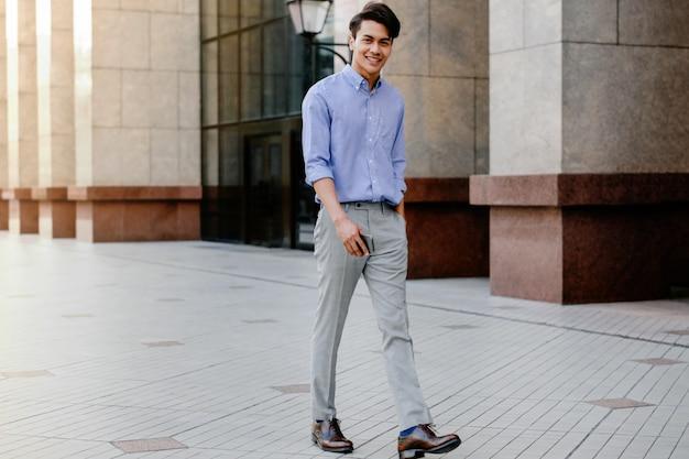 Gelukkig jonge zakenman in vrijetijdskleding wandelen in de stad. levensstijl van moderne mensen.