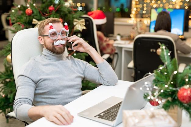 Gelukkig jonge zakenman in xmas bril feliciteren met zakenpartners aan de telefoon door de werkplek op kantoor