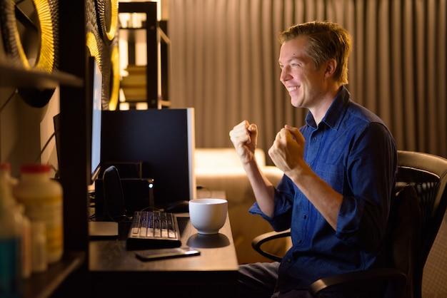 Gelukkig jonge zakenman krijgt goed nieuws tijdens het werken vanuit huis 's avonds laat