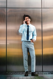 Gelukkig jonge zakenman met behulp van mobiele telefoon in de stedelijke stad. levensstijl van moderne mensen. vooraanzicht. staan bij de muur met koffiekopje.