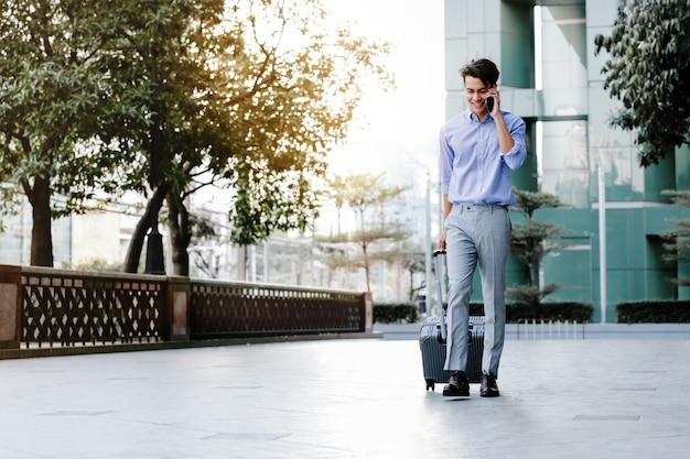 Gelukkig jonge zakenman met behulp van mobiele telefoon tijdens het wandelen met koffer in de stad. levensstijl van moderne mensen. hoge kijkhoek. volledige lengte