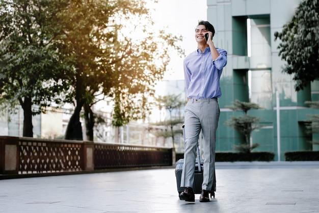 Gelukkig jonge zakenman met behulp van mobiele telefoon tijdens het wandelen met koffer in de stad. levensstijl van moderne mensen. hoge kijkhoek.
