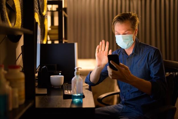 Gelukkig jonge zakenman met masker videobellen met telefoon tijdens het werken vanuit huis 's nachts