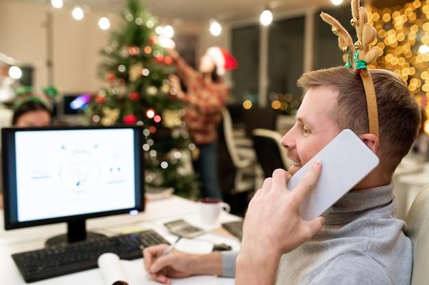 Gelukkig jonge zakenman met xmas hoofdband notities maken tijdens het gesprek op de mobiele telefoon achter computer door werkplek