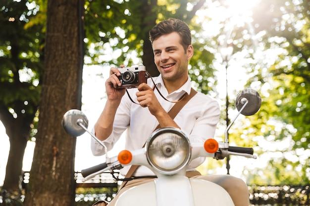 Gelukkig jonge zakenman rijden op een motor buitenshuis, fotograferen met een fotocamera