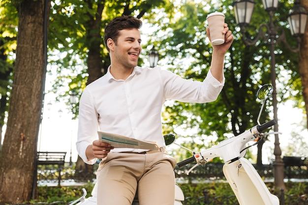Gelukkig jonge zakenman zittend op een motor buitenshuis, krant lezen, koffie drinken, zwaaien