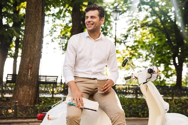 Gelukkig jonge zakenman zittend op een motor buitenshuis, krant lezen, koffie drinken