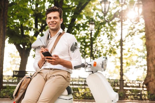 Gelukkig jonge zakenman zittend op een motor buitenshuis, met behulp van mobiele telefoon