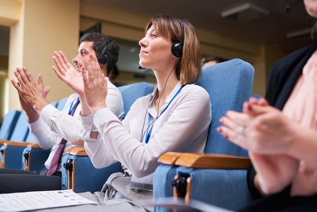 Gelukkig jonge zakenvrouw en haar buitenlandse collega's in koptelefoon zitten in fauteuils en klappen in hun handen na toespraak van afgevaardigde