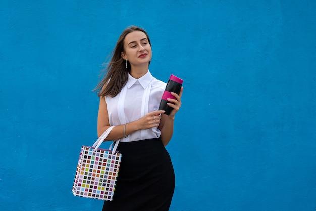 Gelukkig jonge zakenvrouw met boodschappentassen en kopje koffie geïsoleerd op blauwe achtergrond te houden. kopieer ruimte