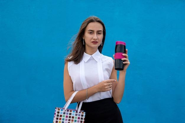 Gelukkig jonge zakenvrouw met boodschappentassen en kopje koffie geïsoleerd op blauwe muur te houden. kopieer ruimte