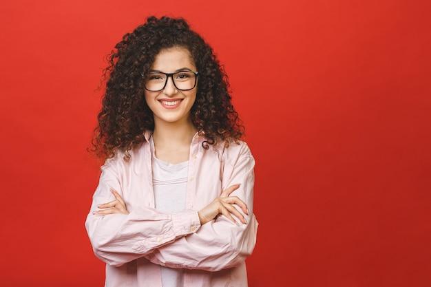Gelukkig jonge zakenvrouw met gekruiste armen en mooie grote glimlach met gezonde tanden. geïsoleerde portret over rode backround.