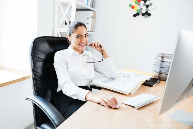 Gelukkig jonge zakenvrouw zit op haar werkplek met een bril en kijkt naar de voorkant
