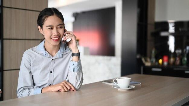 Gelukkig jonge zakenvrouw zittend in een modern kantoor en praten op mobiele telefoon.