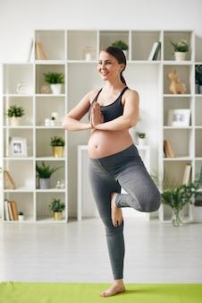 Gelukkig jonge zwangere sportvrouw staande op een been op de mat met haar handen in elkaar gezet door de borst tijdens yoga training thuis