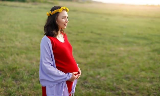 Gelukkig jonge zwangere vrouw lopen in de frisse lucht in de middag in een rode jurk.