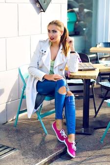 Gelukkig jongedame glimlachend en ontspannen op het terras van de stadscafé, zonnig weer, lichte make-up, stijlvolle casual outfit, vakantie, reizen, vakantie, vreugde.