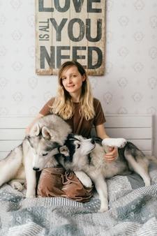 Gelukkig jongedame in bruine jurk zittend op bed en husky puppy's knuffelen.