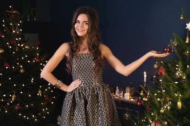 Gelukkig jongedame in de gezellige kamer met kerstversiering