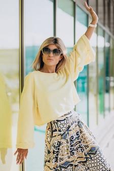 Gelukkig jongedame in gele trui buiten in de stad