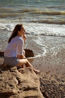 Gelukkig jongedame in wit t-shirt en korte broek zit aan de kust in de zomer