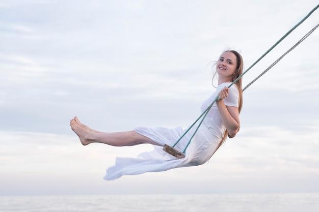 Gelukkig jongedame in witte jurk rijden op een schommel op zee en lucht