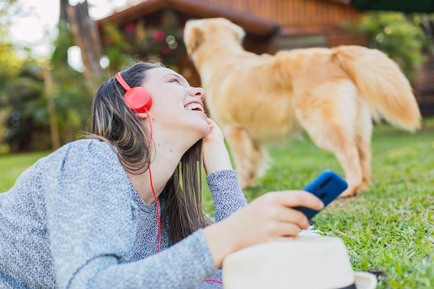 Gelukkig jongedame luisteren naar muziek buitenshuis - mooie jonge vrouw liggend op het gras met koptelefoon en haar hond in de tuin.