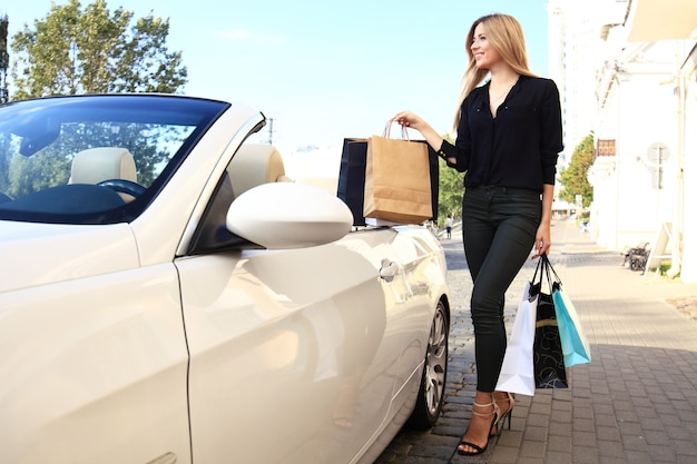 Gelukkig jongedame met boodschappentassen in de buurt van de auto buitenshuis