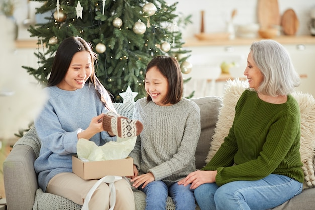 Gelukkig jongedame openen haar kerstcadeau geven door haar moeder en zus tijdens de viering van eerste kerstdag