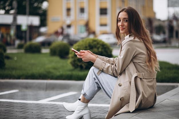 Gelukkig jongedame zitten in het park en praten over de telefoon