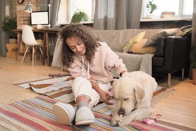 Gelukkig jongedame zittend op de vloer en spelen met haar huisdier in de kamer