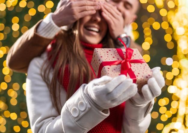 Gelukkig jongeman die de ogen van opgewonden geliefde vriendin bedekt terwijl hij verrassing maakte en kerstcadeau gaf in de buurt van gloeiende boom