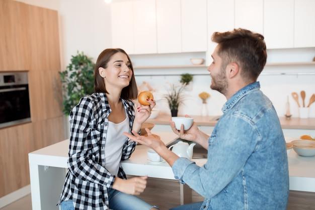 Gelukkig jongeman en vrouw in de keuken aan het ontbijt, paar samen in de ochtend, glimlachen, praten