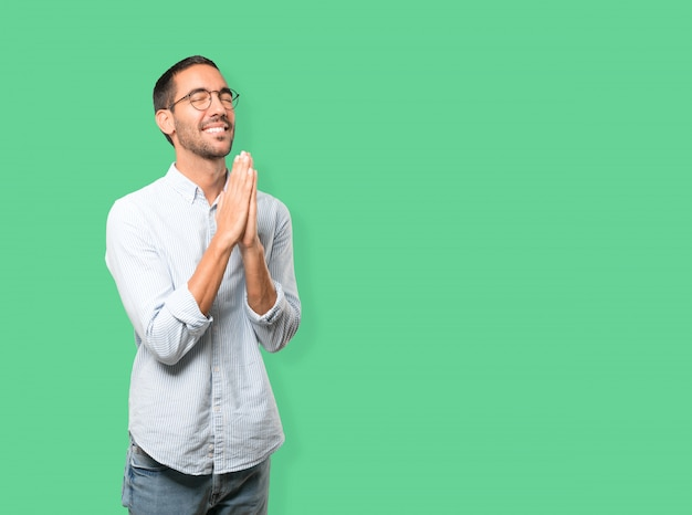 Gelukkig jongeman het bidden gebaar