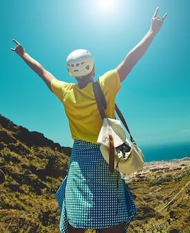 Gelukkig jongeman in stijlvolle kleding op de top van de berg reikt naar de zon
