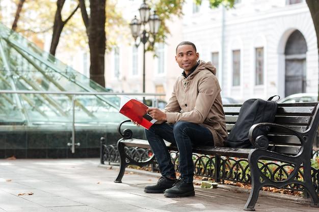 Gelukkig jongeman kijken opzij tijdens het lezen van een boek