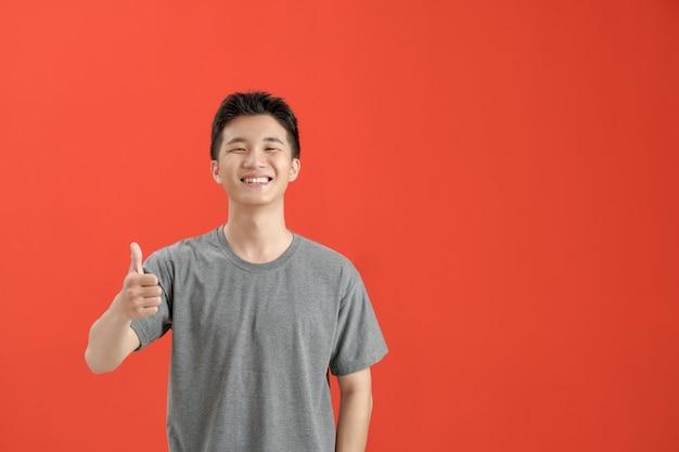 Gelukkig jongeman met duimen omhoog teken in casuals geïsoleerd op rode achtergrond