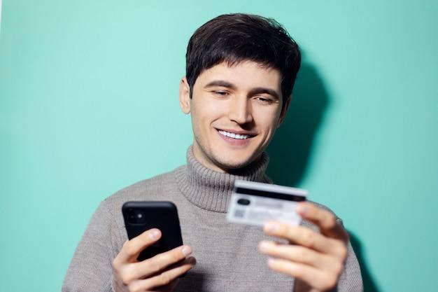 Gelukkig jongeman met smartphone en creditcard in de hand op muur van aqua menthe kleur.