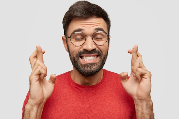 Gelukkig jongeman met stoppels, kruist vingers, houdt de ogen gesloten, gekleed in een rood t-shirt