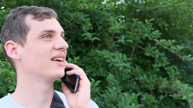 Gelukkig jongeman praten over de achtergrond van de mobiele telefoon van groen