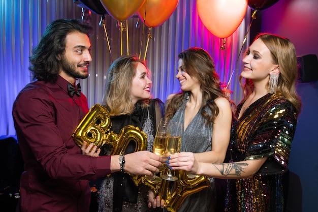 Gelukkig jongeman rammelende fluit champagne met een van de meisjes op verjaardagsfeestje op achtergrond van twee vriendinnen