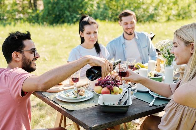 Gelukkig jongeman rode wijn uit de fles gieten in wijnglas van vrij blond meisje zat naast hem door tafel geserveerd tijdens het diner