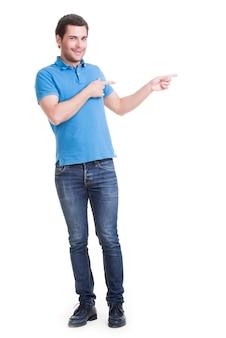 Gelukkig jongeman toont een vinger in de zijkant in volle lengte geïsoleerd op wit.