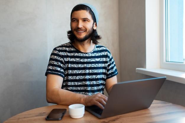 Gelukkig jongeman typen op laptop, thuiswerken. smartphone en koffiekopje op houten tafel. kerel met lang haar die grijze hoed draagt.